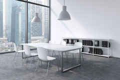 A conference room in a modern panoramic office with Singapore view. White table, white chairs, a bookcase and two white ceiling li Stock Photography