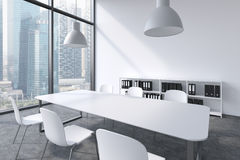A conference room in a modern panoramic office with Singapore view. White table, white chairs, a bookcase and two white ceiling li Stock Images