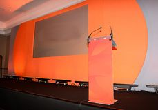 Conference stage and podium. Conference stage  setting with large viewing screen (for video or slide presentation) set in orange painted wall and podium with Stock Photos