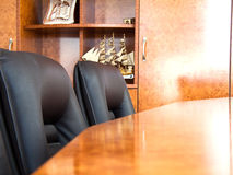 Conference Table. Table from tree and two soft chairs from black skin Royalty Free Stock Photos