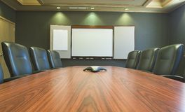 Conference Table w/Blank Whiteboard. A wooden conference table with leather chairs and a blank whiteboard Stock Images