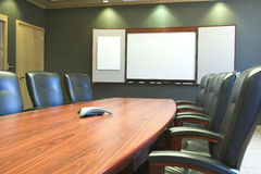 Conference Table w/Blank Whiteboard. A wooden conference table with leather chairs and a blank whiteboard Royalty Free Stock Image