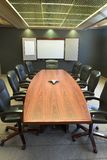 Conference Table w/Blank Whiteboard - vertical. A wooden conference table with leather chairs and a blank whiteboard Stock Photo