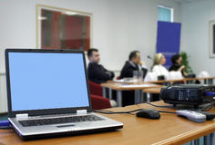 Conference workshop. Room with laptop, video projector and speakers' table Royalty Free Stock Photo