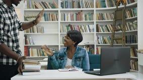 Conferencia africana de la escritura del estudiante mientras que el estudiante masculino del anoter viene a la biblioteca almacen de metraje de vídeo