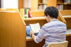 Conferencia asiática joven de la lectura del estudiante universitario en biblioteca Foto de archivo libre de regalías