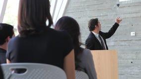 Conferencia de Giving Presentation At del hombre de negocios almacen de video