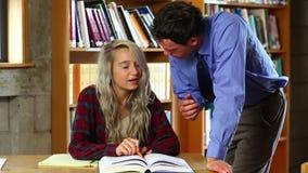 Conferenciante que ayuda al estudiante rubio en la biblioteca almacen de video
