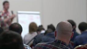 Conferenciante que habla a su clase en la sala de conferencias en la universidad skinhead metrajes