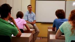 Conferenciante que se sienta y que habla a sus estudiantes en sala de clase almacen de metraje de vídeo