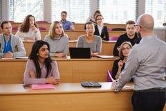 Conferenciante y grupo multinacional de estudiantes en un auditorio foto de archivo libre de regalías
