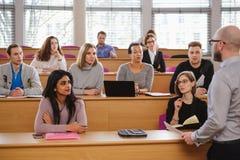 Conferenciante y grupo multinacional de estudiantes en un auditorio fotos de archivo libres de regalías