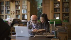 Conferente acadêmico e estudante fêmea que discutem o tema na tabela na biblioteca da universidade vídeos de arquivo