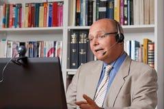 Conferente com computador, câmera e auriculares Imagens de Stock Royalty Free