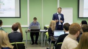 Conferente na sala de aula na universidade que fala a leitura para o grupo de estudantes Orador no terno azul com vídeos de arquivo