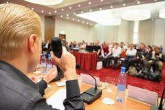 Conferentie in zaal. mens met microfoon. stock fotografie