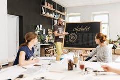 Conferenza ed addestramento nell'ufficio di calligrafia per un gruppo di persone Fotografia Stock Libera da Diritti