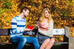 Man confess love to girl on bench in park. Confessing love and affection with romantic gesture. Rejection and disapproval. Negative reaction. Pair sit on bench Royalty Free Stock Photo