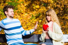 Woman confess love to man on bench in park. Confessing love and affection with romantic gesture. Rejection and disapproval. Negative reaction. Pair sit on bench Stock Photography