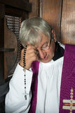 Confession box and priest. Vicar or priest sitting in a confession booth and listening to sins Stock Images