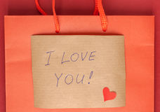Confession letter attached to paper bag. Red heart and confession letter attached to paper bag Royalty Free Stock Image