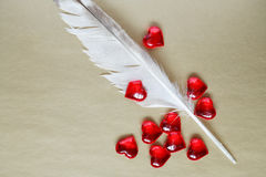 Confession Of Love. Love concept. Quill pen and red hearts on paper background Stock Image
