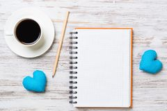 Confession on Valentines day. Coffee cup notepad pencil and two hearts on wooden surface Royalty Free Stock Photos