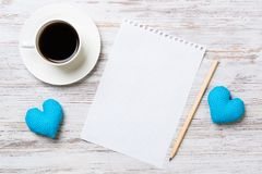 Confession on Valentines day. Coffee cup notepad pencil and two hearts on wooden surface Royalty Free Stock Image