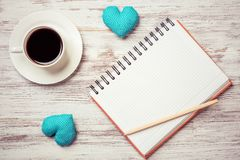 Confession on Valentines day. Coffee cup notepad pencil and two hearts on wooden surface Royalty Free Stock Images