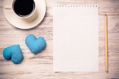 Confession on Valentines day. Coffee cup notepad pencil and two hearts on wooden surface Stock Image