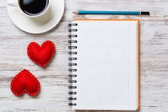 Confession on Valentines day. Coffee cup notepad pencil and two red hearts on wooden surface Royalty Free Stock Photography