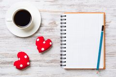 Confession on Valentines day. Coffee cup notepad pencil and two red hearts on wooden surface Royalty Free Stock Image
