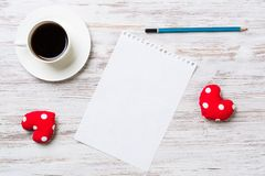 Confession on Valentines day. Coffee cup notepad pencil and two red hearts on wooden surface Royalty Free Stock Photos