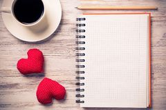 Confession on Valentines day. Coffee cup notepad pencil and two red hearts on wooden surface Stock Images