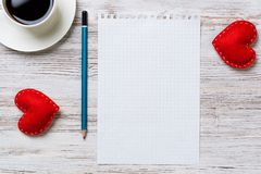 Confession on Valentines day. Coffee cup notepad pencil and two red hearts on wooden surface Royalty Free Stock Images