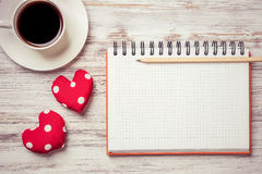 Confession on Valentines day. Coffee cup notepad pencil and two red hearts on wooden surface Stock Photo