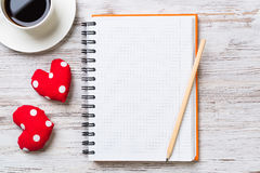 Confession on Valentines day. Coffee cup notepad pencil and two red hearts on wooden surface Royalty Free Stock Photo
