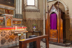 Confessional and altar with candles in the church. Stock Photos