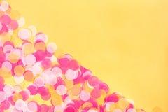 Confete alaranjado, do rosa e o branco no fundo alaranjado fotografia de stock