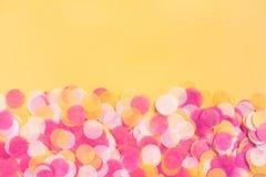 Confete alaranjado, do rosa e o branco no fundo alaranjado imagem de stock