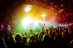 Confetes brilhantes do arco-íris durante o concerto e as silhuetas da multidão com suas mãos acima Fotografia de Stock Royalty Free