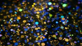 Confetes coloridos cintilantes Defocused do brilho, fundo preto Pontos claros do bokeh festivo abstrato do feriado vídeos de arquivo