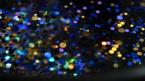 Confetes coloridos cintilantes Defocused do brilho, fundo preto Pontos claros do bokeh festivo abstrato do feriado filme