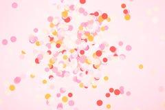 Confetes coloridos no fundo coral imagem de stock royalty free