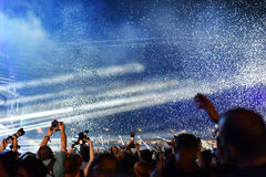 Confetes de jogo sobre a multidão no concerto vivo Imagens de Stock Royalty Free