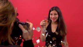 Confetes de sopro da menina modelo a um fotógrafo in camera e levantando com um vidro do champanhe em suas mãos vídeos de arquivo