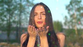 Confetes de sopro da mulher bonita no movimento lento na praia Brilho de sopro do ouro do adolescente feliz caucasiano fora video estoque