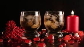 Confetes que caem para baixo movimento lento Dois vidros com o álcool decorado com doces, vela vermelha, close up Romântico ainda vídeos de arquivo