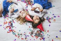Confeti colorido de la moda del niño de dos niñas en el piso Foto de archivo libre de regalías