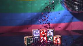 Confeti del corazón que cae en los bloques que deletrean orgullo gay almacen de video